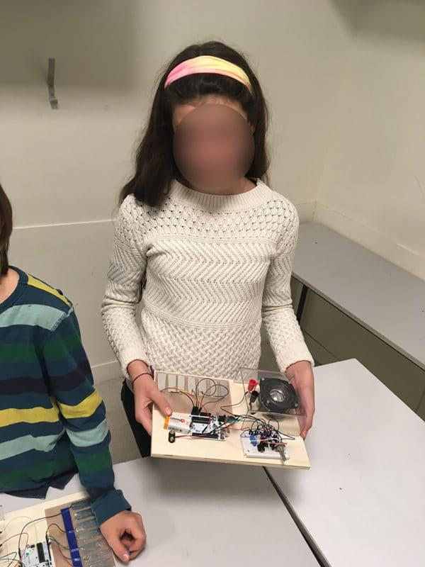 une jeune fille montre son projet l'électronique réussi