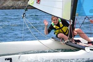 une fille en catamaran en Bretagne salue les animateurs de colonie de vacances