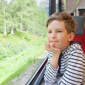 un enfant voyage en train pour se rendre en colonie de vacances