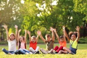 lors d'un voyage scolaire dans la nature des enfants en groupe heureux assis dans l'herbe lèvent les bras au ciel