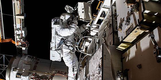 un astronaute de la Nasa en combinaison spatiale répare le vaisseau en sortie dans l'espace