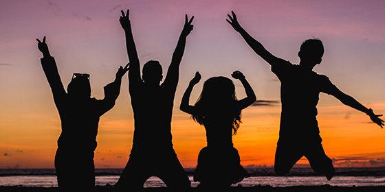 un groupe composé d'enfants et d'adolescents sautent de joie car les vacances débutent
