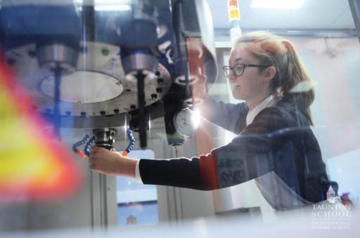 Un enfant fabrique son projet scientifique STEM et manipule une fraiseuse au sein d'un FabLab